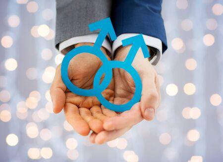 sex: la gente, la homosexualidad, el matrimonio entre personas del mismo sexo y el amor concepto - cerca de la feliz pareja gay masculina sosteniendo recorte de papel amor símbolo durante las vacaciones luces de fondo