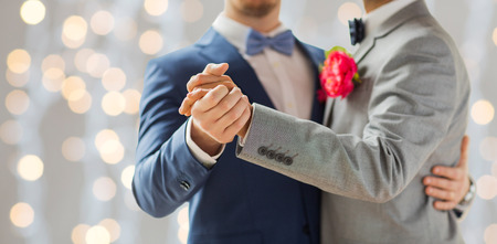 homosexual sex: people, homosexuality, same-sex marriage and love concept - close up of happy male gay couple holding hands and dancing on wedding over holidays lights background
