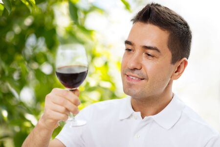 profession, drinks, leisure, holidays and people concept - happy man drinking red wine from glass over green background Stock Photo