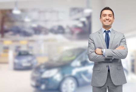 sales person: business, car sale, consumerism and people concept - happy man over auto show or salon background Stock Photo