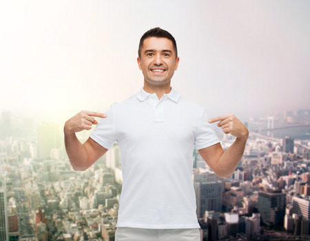 polo t shirt: happiness, advertisement, fashion, gesture and people concept - smiling man in t-shirt pointing fingers on himself over city background