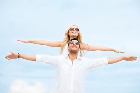 anniversary beach: summer holidays and dating concept - couple holding hands up at sea side Stock Photo