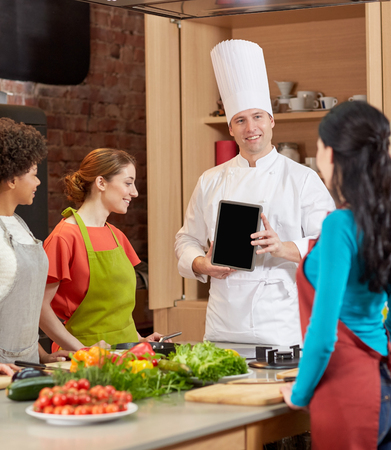 cooking class, culinary, food, technology and people concept - happy women with chef cook showing blank tablet pc screen in kitchen photo