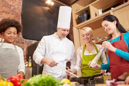 hombre cocinando: clase de cocina, culinario, comida y gente concepto - feliz grupo de mujeres y masculino chef cocinero cocina en cocina Foto de archivo