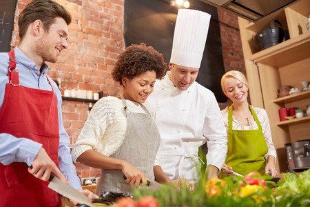 kitchen aprons: cooking class, culinary, food and people concept - happy group of friends and male chef cook cooking in kitchen Stock Photo