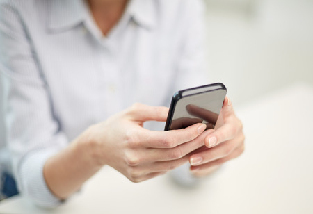 business, technology and people concept - close up of woman hands texting message on smartphone at office