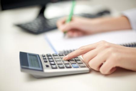 Finanzen, Wirtschaft, Technologie und Menschen Konzept - Nahaufnahme von Frau Hände mit Taschenrechner Zählen und Notizen zu Notebooks Standard-Bild