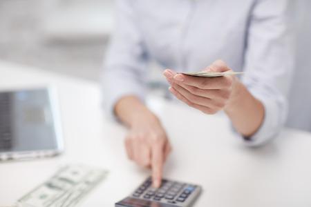 besparingen, financiën, economie, technologie en mensen concept - close-up van vrouw tellen geld met rekenmachine Stockfoto