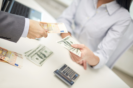 finances, currency, exchange rate, business and people concept - close up of male and female hands giving or exchanging money at office