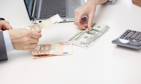 finances, currency, exchange rate, technology and people concept - close up of hands counting dollar and euro money at office Stock Photo