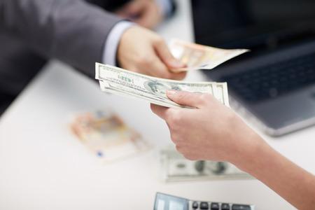 financiën, valuta, wisselkoersen, het bedrijfsleven en mensen concept - close-up van mannelijke en vrouwelijke handen geven of geld wisselen op het kantoor