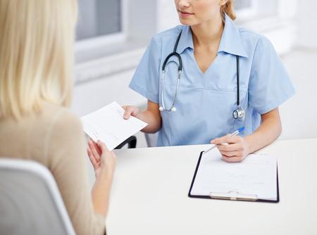 lekarz: medycyny, ochrony zdrowia, spełnienia i koncepcja ludzie - bliska lekarz z schowka dając receptę lub świadectwo młodej kobiety w szpitalu Zdjęcie Seryjne