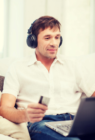 new age music: technology, leisure and lifestyle concept - happy man with headphones and credit card listening to music at home