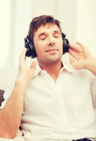 new age music: leisure and lifestyle concept - happy man with headphones listening to music at home