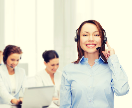 helpline: business, technology and call center concept - friendly female helpline operator with headphones at office