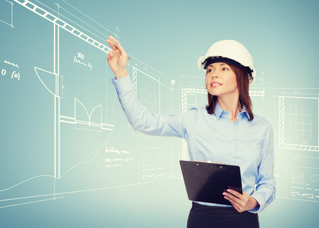 business outline: building, developing, consrtuction and architecture concept - smiling businesswoman in white helmet with clipboard pointing finger Stock Photo