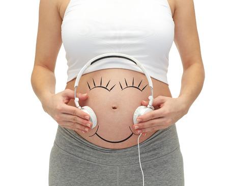 Schwangerschaft, Menschen, Musik, Technik und Erwartung Konzept - Nahaufnahme von glücklichen schwangeren Frau, die Kopfhörer auf Bauch kahl Standard-Bild - 38675454