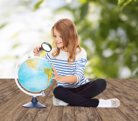 human geography: education, travel, childhood, geography and school concept - happy little student girl looking at globe with magnifier over green background