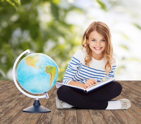 human geography: education, geography, childhood, people and school concept - little student girl studying with globe and book over green background Stock Photo