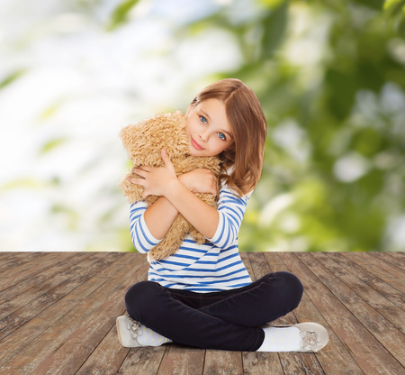 childhood, toys and people concept - cute little girl hugging teddy bear over greed background