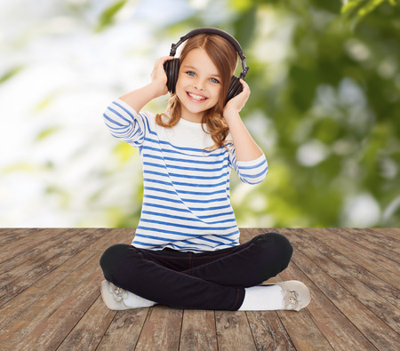 pre teen girls: music, childhood, people and technology concept - happy girl with headphones listening to music over greed background Stock Photo