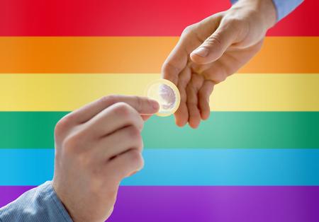 sexual education: personas, homosexualidad, sexo seguro, de educación sexual y de concepto de caridad - Cerca de feliz varones homosexuales par manos dando condón sobre el arco iris fondo de la bandera