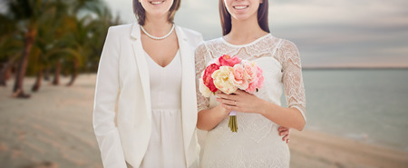 people, homosexuality, same-sex marriage, honeymoon and love concept - close up of happy married lesbian couple with flower bunch over tropical beach background