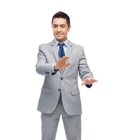 imaginary: business, people and office concept - happy smiling businessman in suit touching something imaginary