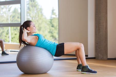 gym: fitness, deporte, el entrenamiento y la gente concepto - mujer sonriente que dobla los m�sculos abdominales con pelota de ejercicio en el gimnasio Foto de archivo