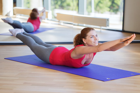 fitness, sport, training and people concept - smiling woman doing back extension exercise on mat in gym