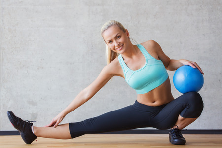 mujer alegre: fitness, deporte, el entrenamiento y la gente concepto - mujer sonriente con bola de ejercicio en el gimnasio Foto de archivo