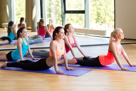 ejercicio aer�bico: fitness, deporte, entrenamiento y estilo de vida concepto - grupo de mujeres sonrientes estiramiento en el gimnasio