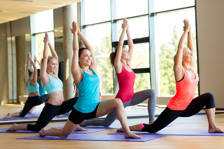 aerobics class: fitness, sport, training and lifestyle concept - group of smiling women stretching in gym