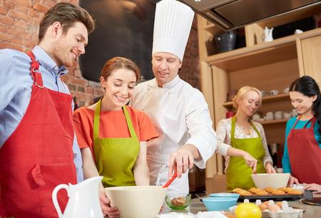 kulinarne: Klasa gotowanie, kulinarne, piekarnia, żywność i koncepcja ludzie - happy grupa przyjaciół i mężczyzn kucharz pieczenia w kuchni