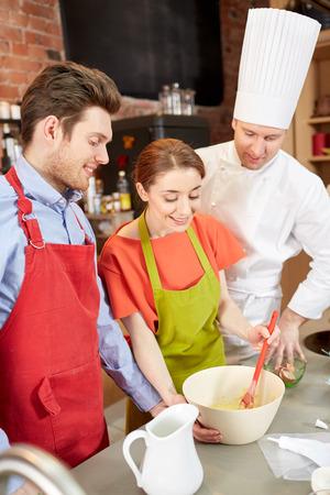 hombre cocinando: clase de cocina, panadería, cocción de alimentos y la gente concepto - pareja feliz y masculino chef cocinero crema prepearing o masa en la cocina Foto de archivo