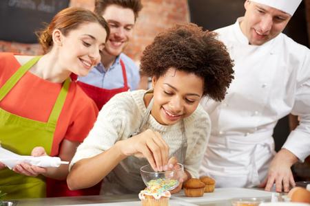 chef: clase de cocina, culinario, panadería, comida y gente concepto - feliz grupo de amigos y cocinero de sexo masculino cocinar hornear en la cocina Foto de archivo