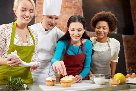 mujeres cocinando: clase de cocina, culinario, panadería, comida y gente concepto - feliz grupo de mujeres y cocinero de sexo masculino cocinar hornear en la cocina