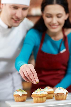 decoracion de pasteles: clase de cocina, culinario, panadería, comida y gente concepto - grupo feliz de la mujer y el chef Cocinero de sexo masculino de hornear en la cocina