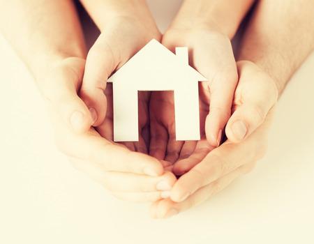 planificación familiar: gd de hombre y mujer de las manos que sostienen la casa de papel Foto de archivo