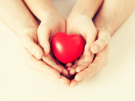holding close: close up of woman and man hands with heart