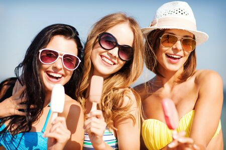 tanned girl: summer holidays and vacation - girls in bikinis eating ice cream on the beach Stock Photo