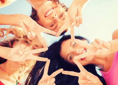 Verano, vacaciones, vacaciones, feliz a la gente concepto - grupo de chicas que miran abajo y mostrando el dedo cinco gesto Foto de archivo - 38675881