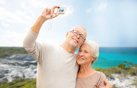 retired couple: age, tourism, travel, technology and people concept - senior couple with camera taking selfie on street over beach background