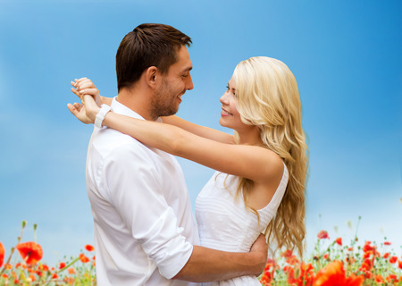 summer holidays, people, love and dating concept - happy couple hugging over blue sky and poppy field background photo