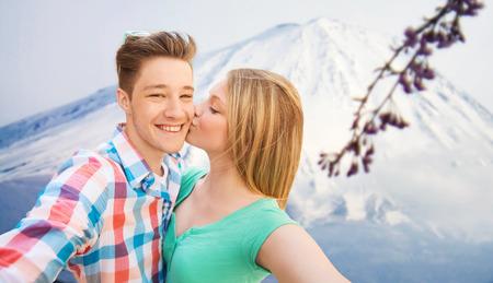 novios besandose: viaje, vacaciones, la tecnología, las personas y el concepto de amor - sonriente pareja con el teléfono inteligente más de japón montañas de fondo