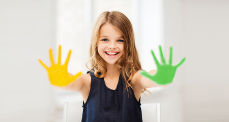 pre teen girl: education, school, art and happiness concept - little student girl showing hands in yellow and green color at school