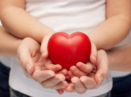 kids holding hands: people, charity, family and advertisement concept - close up of woman and girl holding  red heart shape in cupped hands Stock Photo