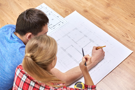 floor plans: repair, building, renovation and people concept - close up of happy couple looking at blueprint at home