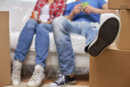 people moving: moving, home, repair and people concept - close up of couple legs relaxing and sitting on sofa with cups in new apartment Stock Photo