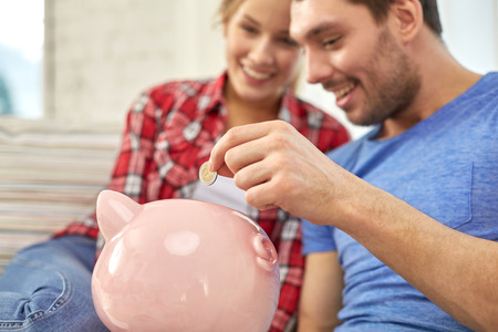 bank: money, home, finance and relationships concept - close up of couple with piggy bank sitting on sofa